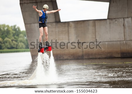 Young man using flyboard machine on river  - stock photo