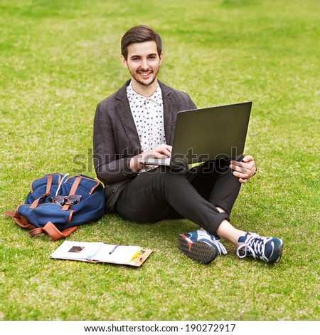 Young man using his laptop on the grass and makes notes in a notebook - stock photo