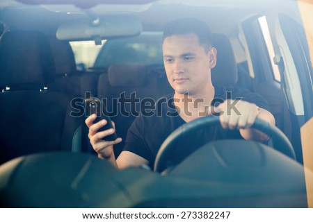 Young man using his smartphone behind the wheel. Shot through the windshield - stock photo