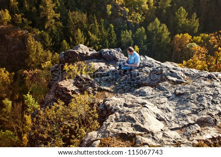 young man using laptop sitting on a rock slope - stock photo
