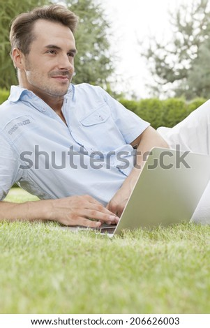 Young man using laptop while looking away in park - stock photo