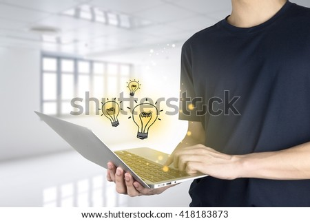 Young man using laptop with light bulb on light white room background - stock photo