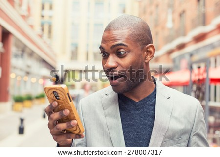 Young man using smart phone. Businessman holding mobile smartphone using app texting sms message wearing jacket - stock photo