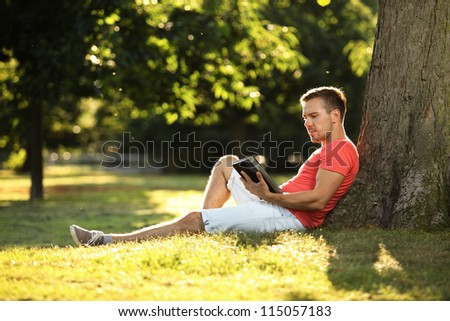 young man using tablet in park - stock photo