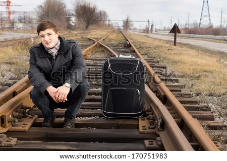 Young man waiting for a train at a rural siding squatting in the centre of the track with his suitcase balancing on the wooden sleepers - stock photo
