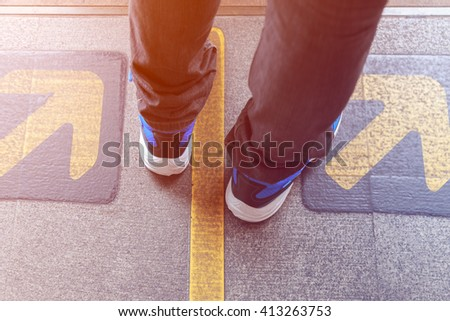 Young man waiting skytrain standing between the yellow arrows - stock photo