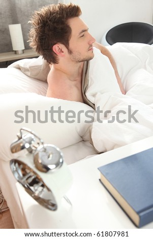 Young man waking up - stock photo