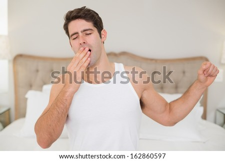 Young man waking up in bed and stretching his arms at home - stock photo