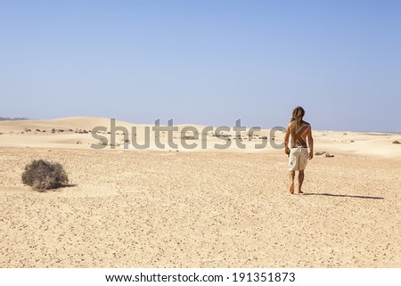 young man walking alone in the desert - stock photo