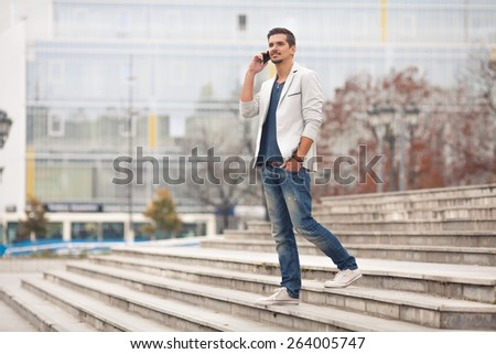 Young man walking down the stairs and talking on the phone - stock photo