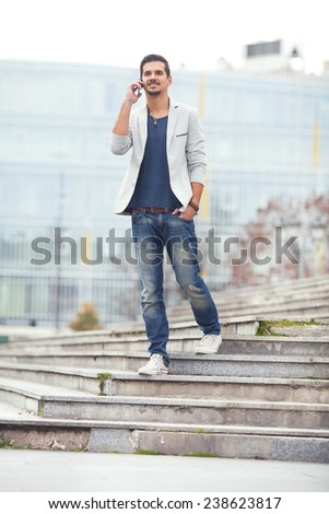 Young man walking down the stairs talking on the phone - stock photo