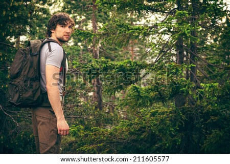 Young Man walking in forest with backpack Hiking Lifestyle and outdoor recreation concept - stock photo