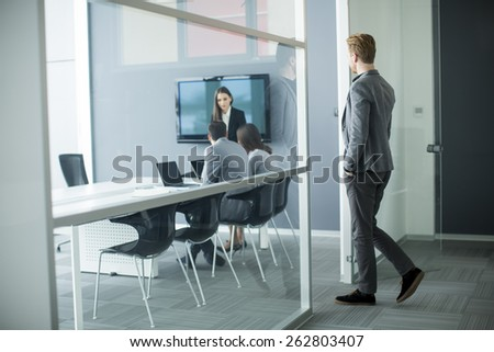 Young man walking into office - stock photo