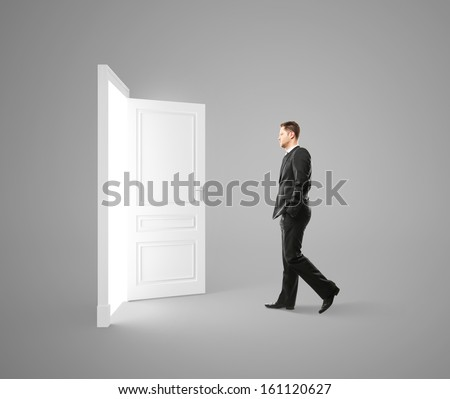 young man walking to opened door - stock photo