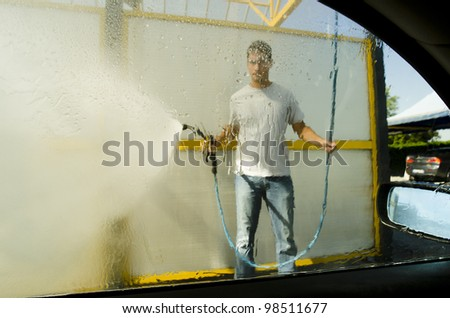 Young man washing a car using compression water - stock photo