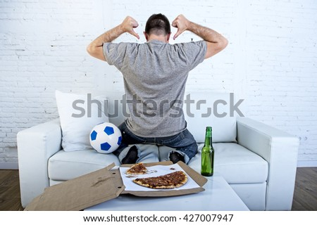 young man watching football game on television celebrating goal crazy happy jumping on sofa couch at home with ball beer bottle and pizza looking excited  pointing her back like the player - stock photo