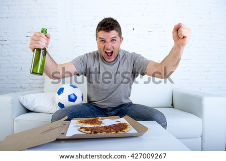 young man watching football game on television celebrating goal crazy happy jumping on sofa couch at home with ball holding beer bottle eating pizza looking excited and cheerful - stock photo