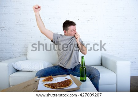 young man watching football game on television celebrating goal crazy happy  on sofa couch at home with ball beer bottle and pizza looking excited and cheerfull kissing his team shield - stock photo