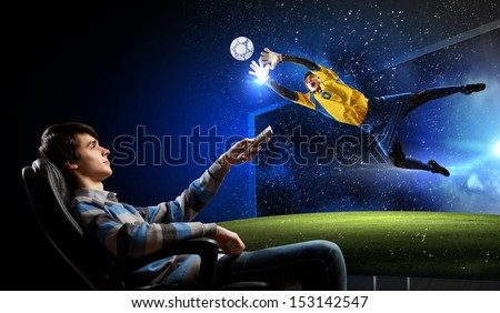Young man watching football match on TV - stock photo