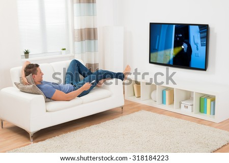 Young Man Watching Movie On Television In Living Room - stock photo