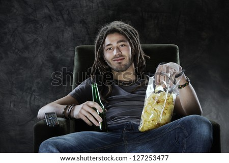 Young man watching television eating potato chips and drinking beer - stock photo