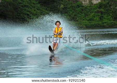 Young man water skiing - stock photo