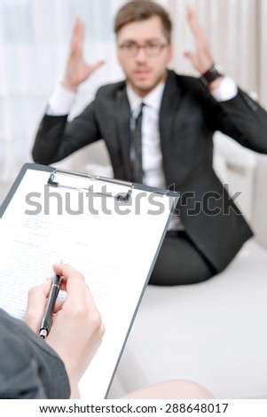 Young man wearing a black suit sitting on a couch shouting nervous explaining his problems, psychologist with clipboard listening to him and making notes during therapy session, selective focus - stock photo