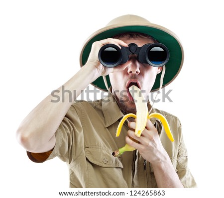 Young man wearing a pith helmet looking through a pair of binoculars and eating banana, isolated on white - stock photo
