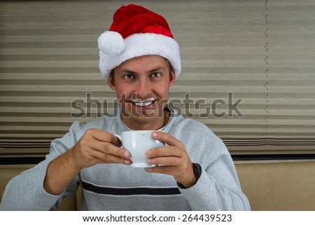 young man wearing a santa hat  drinking hot chocolate with foam on the upper lip - stock photo