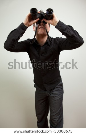 Young man wearing black shirt and holding binoculars, isolated on white - stock photo