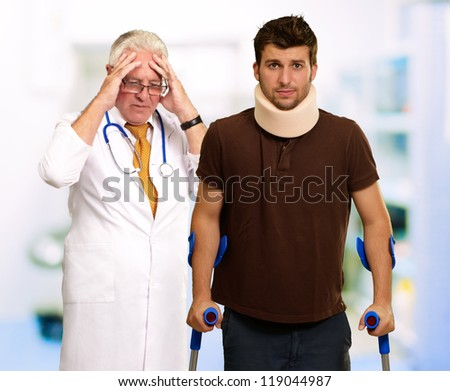 Young Man Wearing Cervical Collar And Frustrated Doctor Behind It, Indoors - stock photo