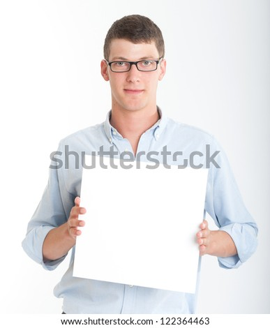 Young man wearing glasses holding a blank square, perfect for inserting your own message - stock photo