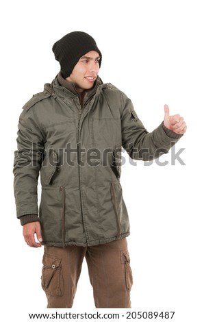young man wearing green winter coat and a beanie hitchhiking isolated on white - stock photo