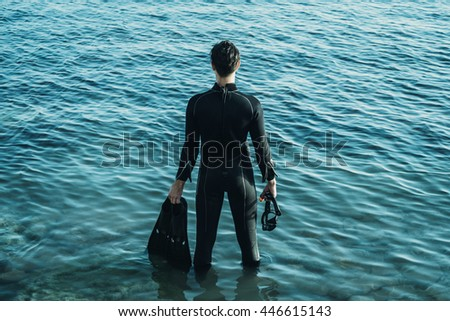 Young man wearing in a diving suit with flippers standing in the sea in summer, rear view - stock photo
