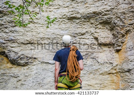 Young man wearing in climbing equipment with rope standing in front of a stone rock and preparing to climb - stock photo