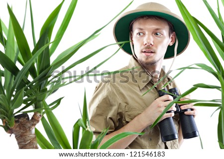 Young man wearing pith helmet holding binoculars and staring at something amazing, palm trees on foreground out of focus, isolated on white - stock photo