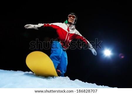 Young man wearing ski mask balancing on snowboard - stock photo