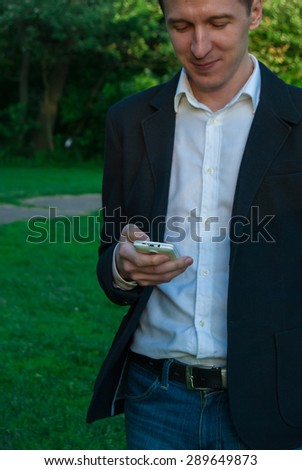 Young man wearing suit looks at his smartphone, outdoors on the green background of trees and bushes. Business man in a green zone or park. An image for topics of finance, business and communication - stock photo