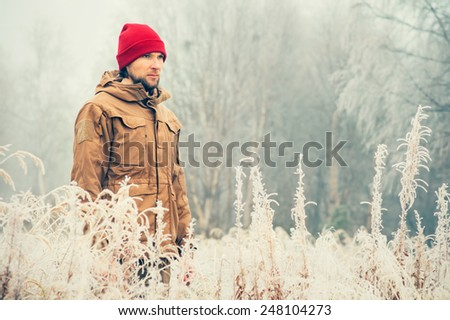 Young Man wearing winter hat clothing outdoor with foggy forest nature on background Travel Lifestyle and melancholy emotions concept film effects colors - stock photo