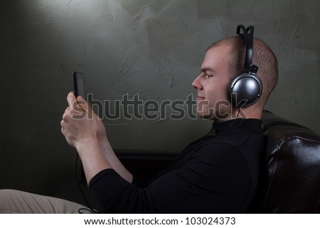 young man well dressed listens to music on a tablet - stock photo
