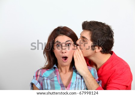Young man whispering in his girlfriend's ear - stock photo