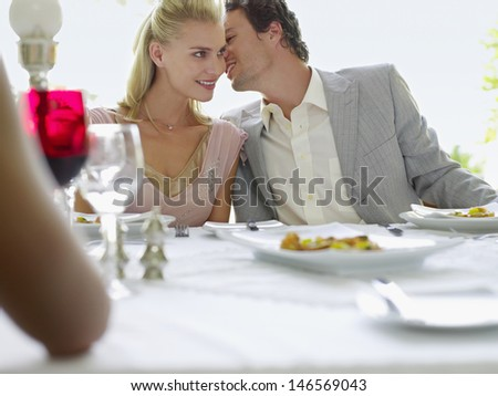 Young man whispering into woman's ear at dinner party - stock photo