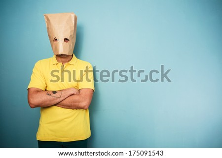 Young man with a bag over his head standing with his arms crossed and looking grumpy - stock photo