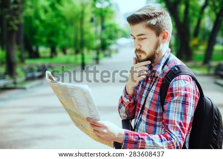 Young man with a beard holding a map and thinking, outdoors in the alley of the park, profile - stock photo