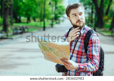 Young man with a beard holding a map looking to the side and thinking, outdoors in the alley of the park - stock photo