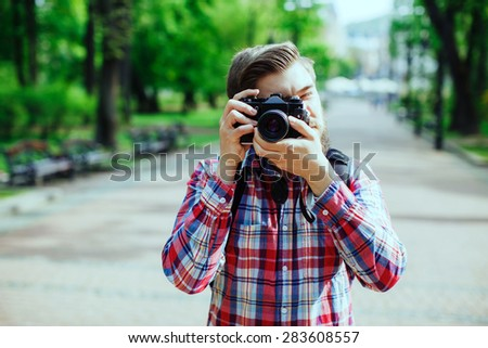 Young man with a beard taking photos on old film camera outdoors in the alley, in the park, central frame - stock photo