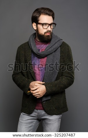 Young man with a beard, wearing a jacket and jeans standing - stock photo