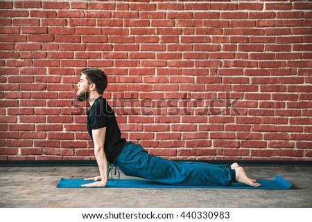 Young man with a beard wearing black T-shirt and blue trousers doing yoga position on blue matt at wall background, copy space, cobra asana, bhujangasana - stock photo