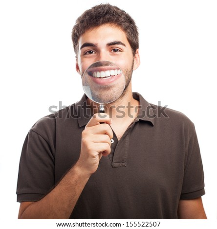 young man with a big mouth because of magnifying glass - stock photo