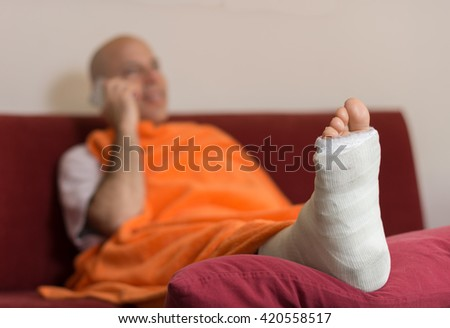 Young man with a broken ankle and a white cast on his leg, talking on his mobile phone on a red couch, covered with an orange comforter (selective focus) - stock photo
